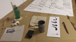 Materials on the worktable to begin adding script to a series of posters.