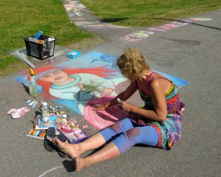 Mary Jean Crowe, artist, draws part of her painting, Eve's Garden, at the Belfast Chalk Walk 2017