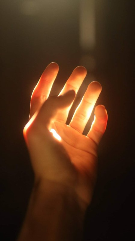 Inspiration Photo by Elia Pellerini of a hand with a deep dark brown background.
